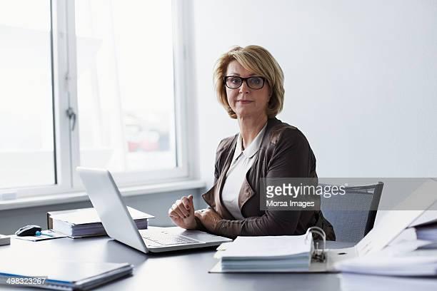 confident businesswoman sitting at desk - mittellanges haar stock-fotos und bilder