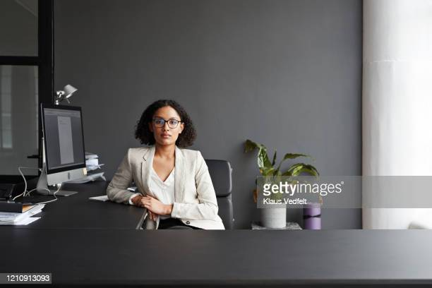 confident businesswoman sitting at office desk - black hair stock pictures, royalty-free photos & images