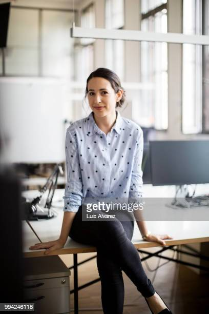 confident businesswoman sitting on desk - vertikal stock-fotos und bilder