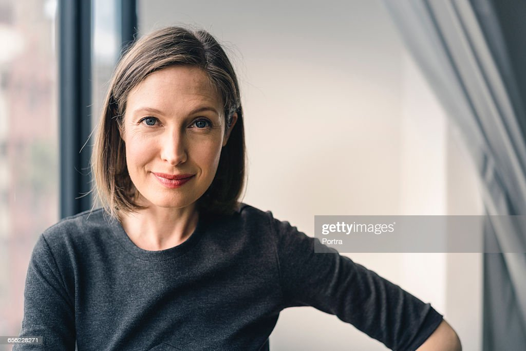 Confident businesswoman smiling in office : Stock Photo