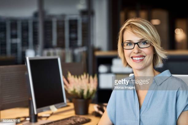 confident businesswoman smiling in office - part of a series stock pictures, royalty-free photos & images