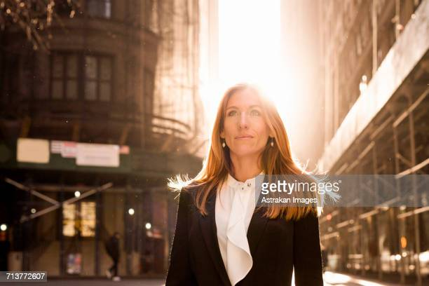 confident businesswoman standing against buildings during sunny day - wall street stock photos and pictures