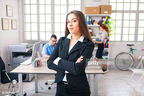 Confident businesswoman standing arms crossed at workplace