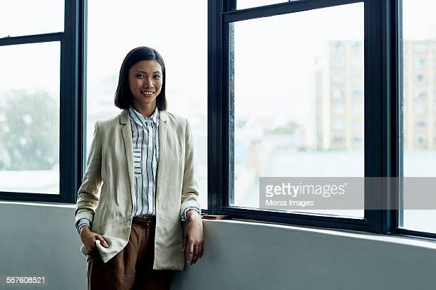 Confident businesswoman standing by office window