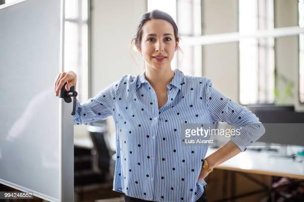 confident businesswoman standing by whiteboard - 30 34 jahre stock-fotos und bilder