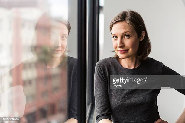 Confident businesswoman standing by window