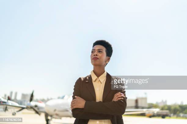 confident businesswoman standing in airport hangar with arms crossed - chairperson stock pictures, royalty-free photos & images