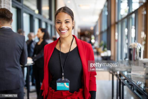 confident businesswoman standing in convention center - identity card stock pictures, royalty-free photos & images
