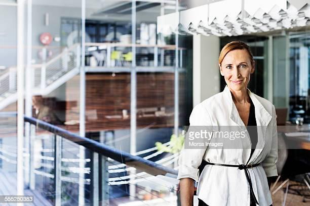 confident businesswoman standing in office - femme 50 ans brune photos et images de collection