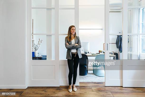 confident businesswoman standing in office - standing photos et images de collection