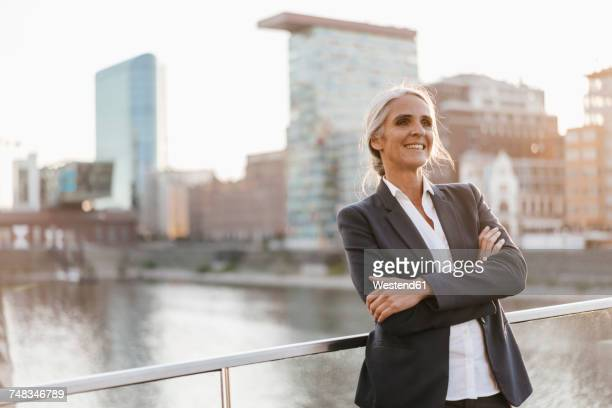 confident businesswoman standing on bridge - geschäftskleidung stock-fotos und bilder