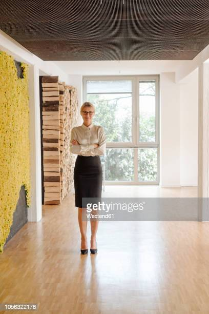 confident businesswoman standing on office floor - one mature woman only stock pictures, royalty-free photos & images