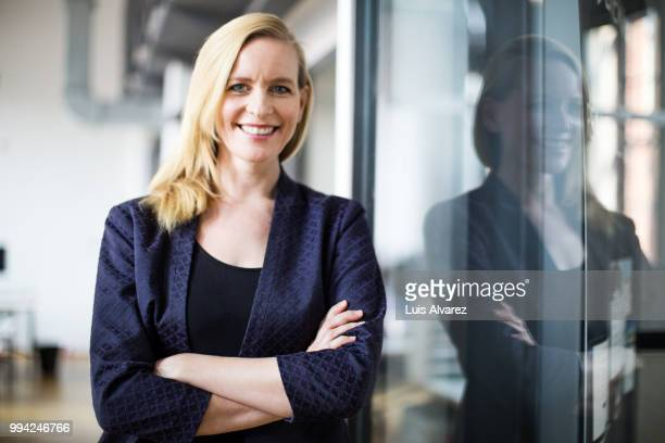 Confident businesswoman standing with arms crossed