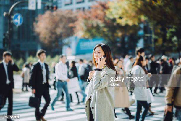 confident businesswoman talking on mobile phone in busy financial district in city - japan commuters ストックフォトと画像