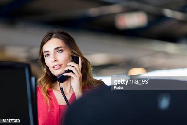 Confident businesswoman talking on phone at office