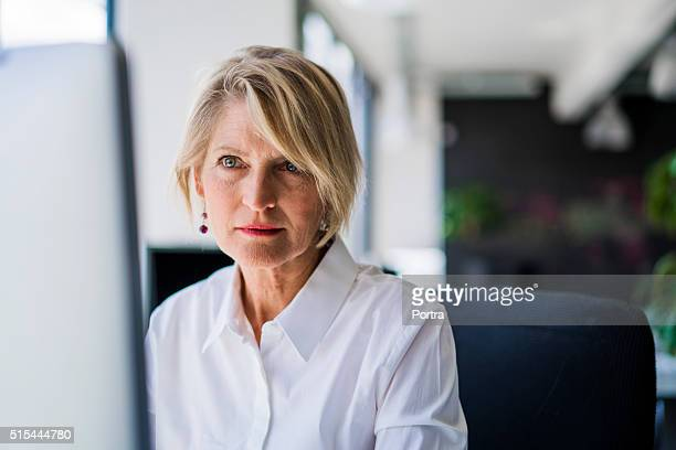 confident businesswoman using computer - 50 59 years stock pictures, royalty-free photos & images