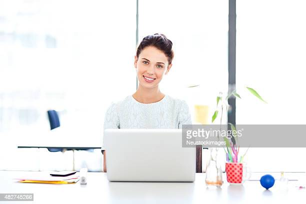 Confident Businesswoman Using Laptop At Desk In Office