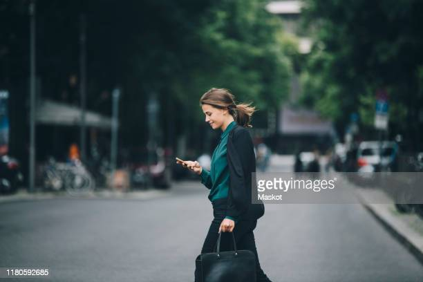 confident businesswoman using smart phone while crossing street in city - zakenvrouw stockfoto's en -beelden