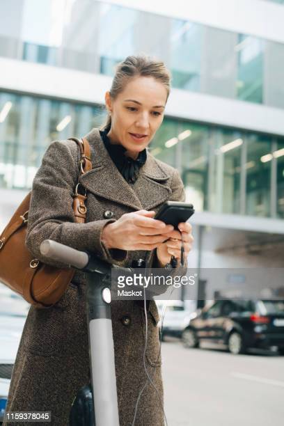 confident businesswoman using smart phone while standing with electric push scooter in city - western europe stock pictures, royalty-free photos & images