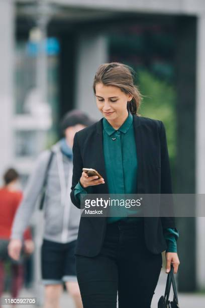 confident businesswoman using smart phone while walking on street in city - incidental people stock pictures, royalty-free photos & images