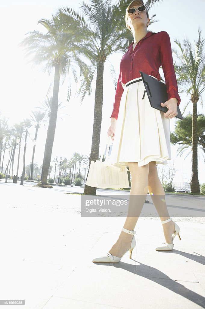 Confident Businesswoman Walks Down an Avenue Carrying a Clipboard : Stock Photo