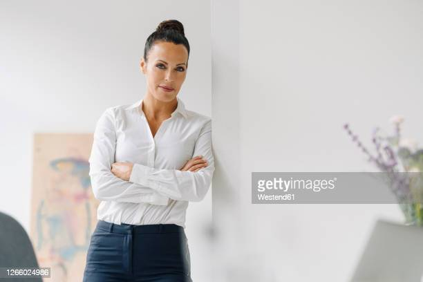 confident businesswoman with arms crossed standing by wall in home office - front view stock pictures, royalty-free photos & images