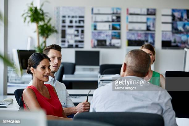 confident businesswoman with colleagues in meeting - red background stock photos and pictures
