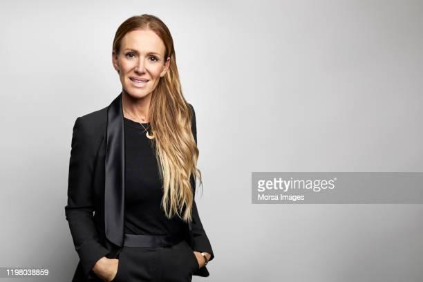 confident businesswoman with hands in pockets - bürokleidung stock-fotos und bilder