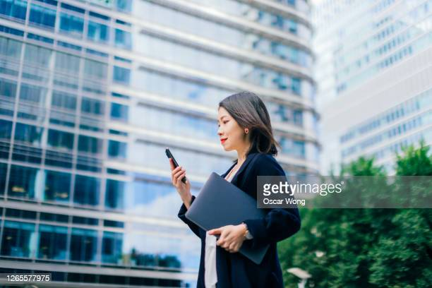 confident businesswoman with smart phone and laptop walking outside office building - cityscape stock pictures, royalty-free photos & images