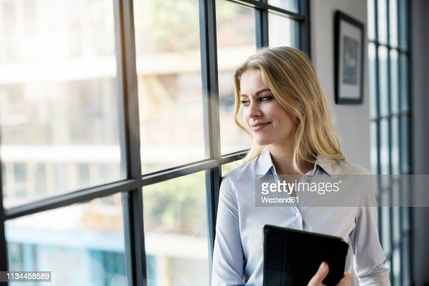 confident businesswoman with tablet in office looking out of window - geschäftskleidung stock-fotos und bilder