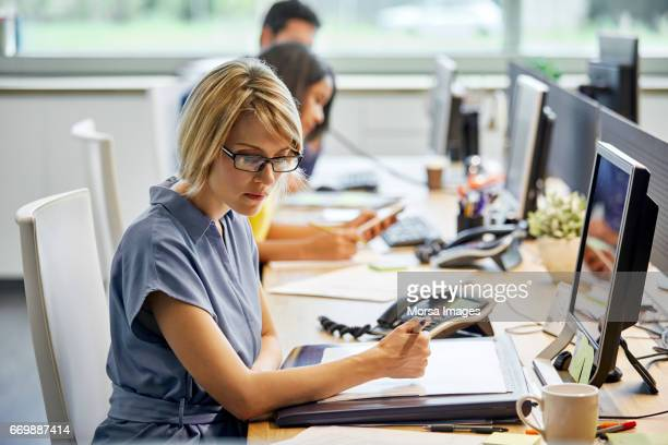 confident businesswoman working at desk - colletti bianchi foto e immagini stock