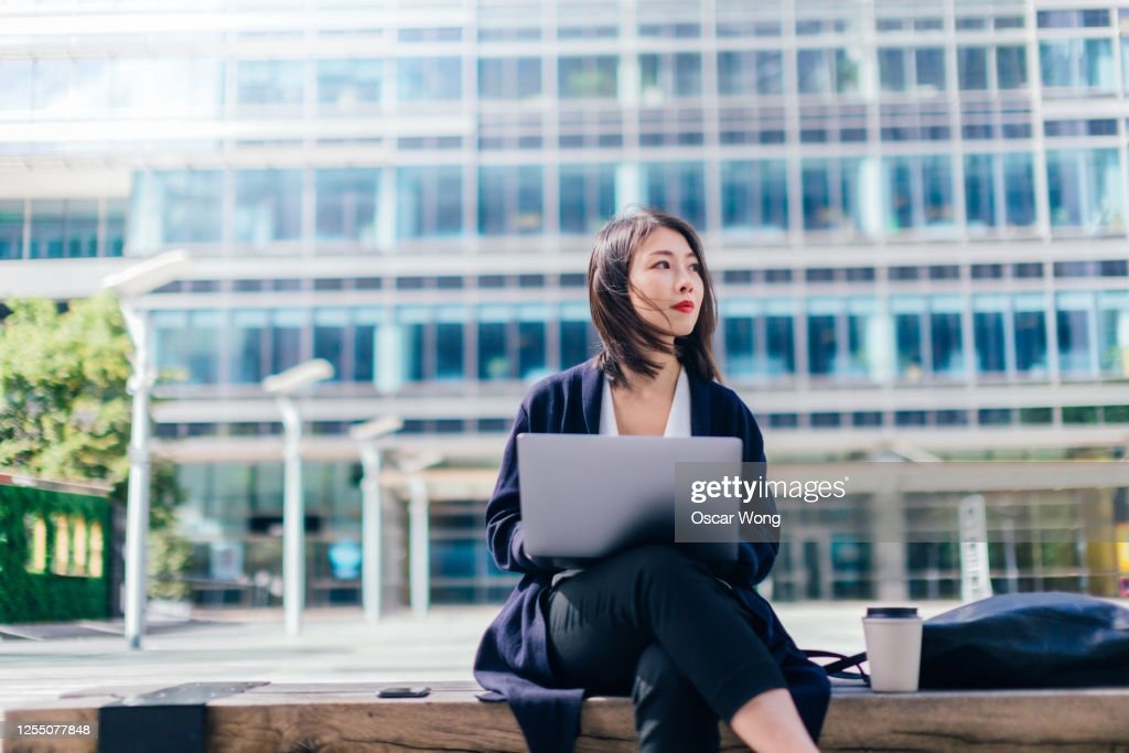 Confident Businesswoman Working With Laptop In The Financial District : Stock Photo