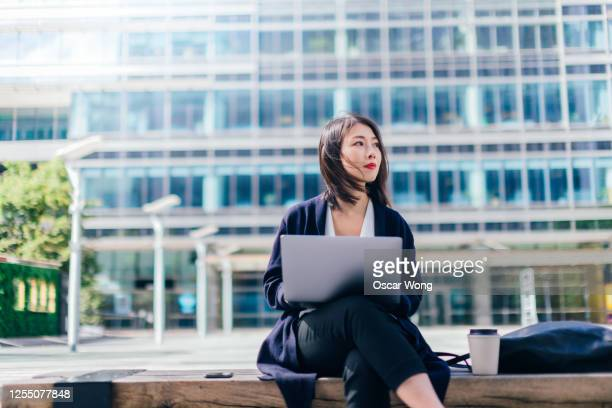 confident businesswoman working with laptop in the financial district - contemplation stock pictures, royalty-free photos & images