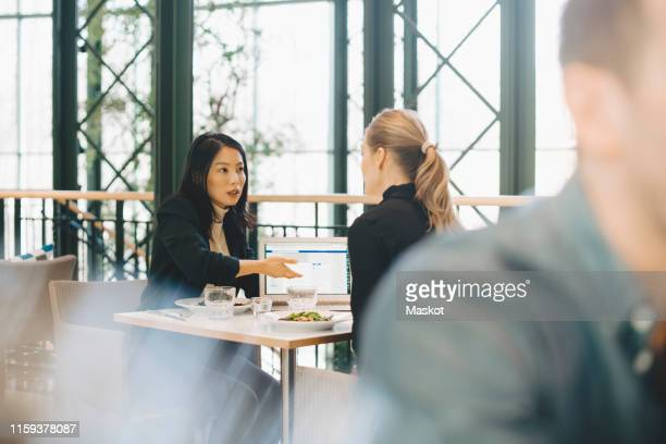 confident businesswomen planning strategy at table during meeting in cafeteria - lunch foto e immagini stock