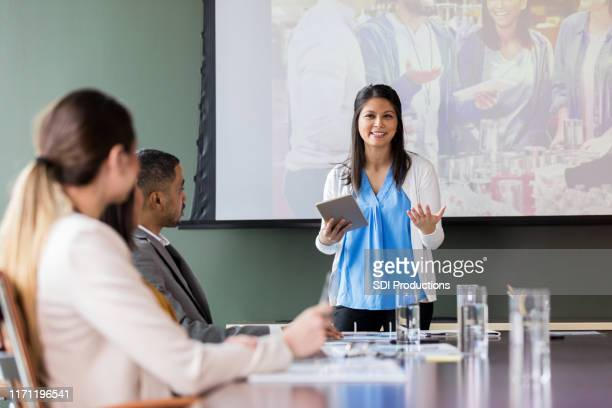 confident busineswwoman discusses charity event - non profit organization stock pictures, royalty-free photos & images