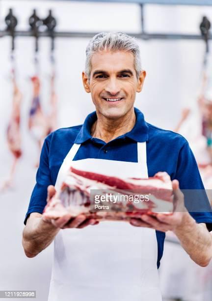 boucher confiant retenant la viande rouge fraîche - boucher photos et images de collection