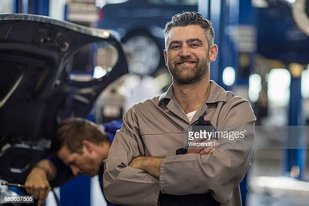 Confident car mechanic in repair garage