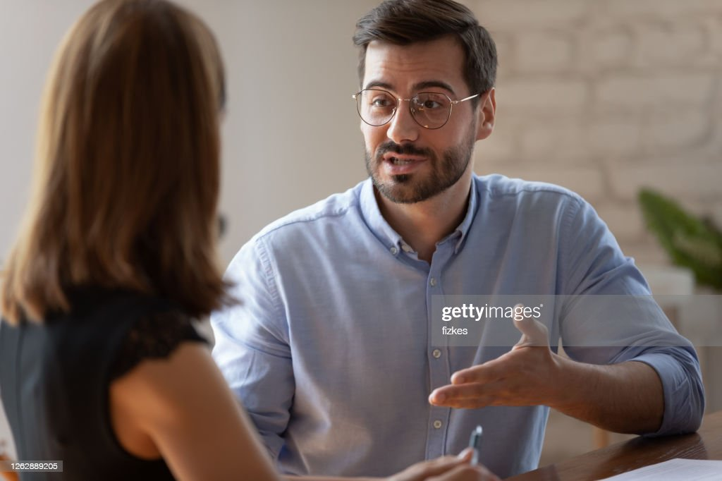 Confident caucasian male applicant answering on questions during job interview : Stock Photo