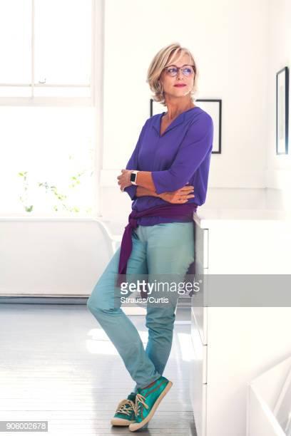 confident caucasian woman leaning on cabinet - lehnend stock-fotos und bilder