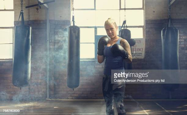 confident caucasian woman posing near punching bags in gymnasium - combat sport stock pictures, royalty-free photos & images