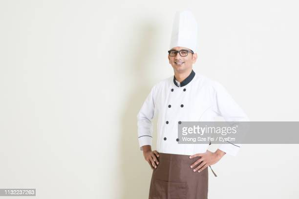 confident chef wearing uniform standing against wall - コック帽 ストックフォトと画像