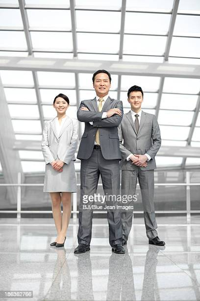 Confident Chinese business people in airport lobby