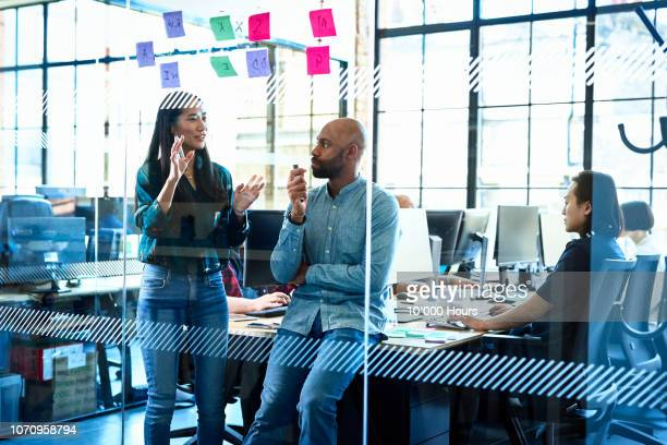 confident chinese woman talking to colleague in office - innovation stock-fotos und bilder
