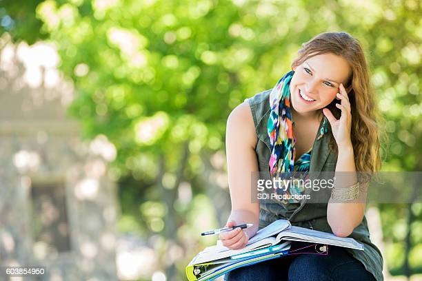 Confident college girl works on assignment on campus