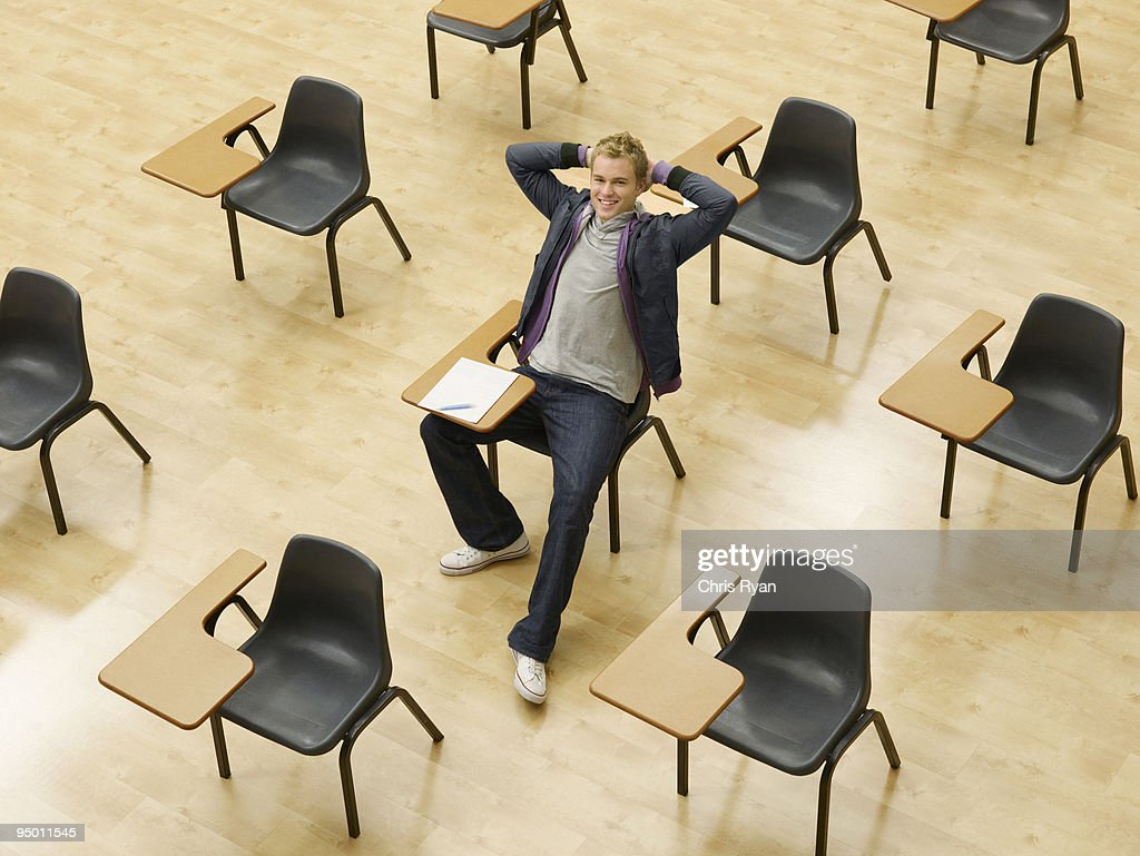 Confident college student sitting at desk in classroom : Stock Photo