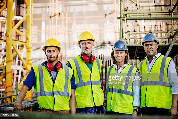confident construction team standing at site - work helmet stock pictures, royalty-free photos & images