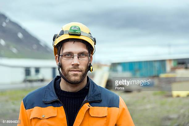 Confident construction worker at wearing hardhat