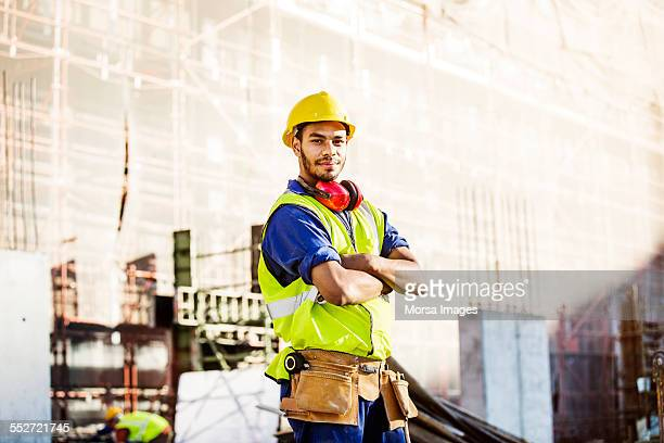 Confident construction worker standing at site