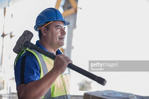 Confident construction worker with sledgehammer