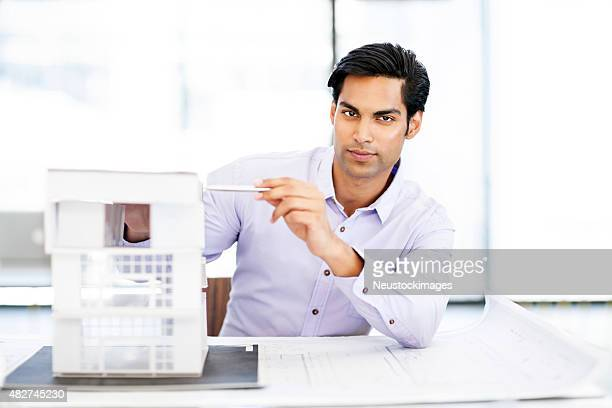 Confident Contractor Analyzing House Model At Desk
